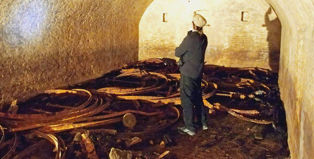 In Cave Two, iron rings at author Marlin Ingalls' feet are the remains of beer vats destroyed in a fire.