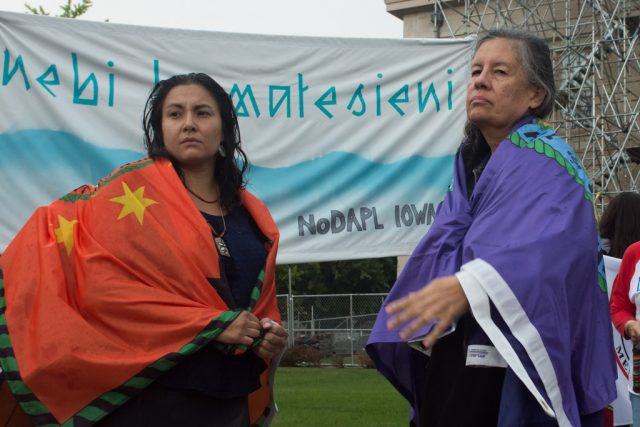 Christine Nobliss and Jacki Rand stand wrapped in flags of native tribes on the Pentacrest. Thursday, Sept. 22, 2016. -- photo by Zak Neumann