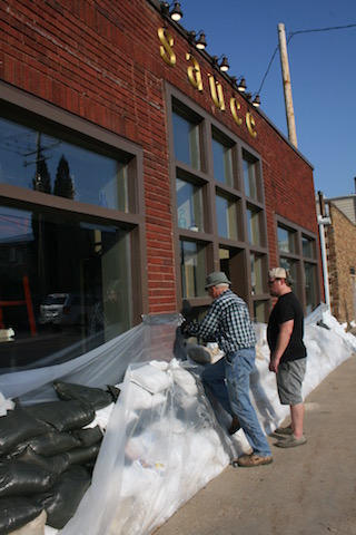 Rick Yoerger and Sauce co-owner Chris Robinson work on building up the wall of sandbags surrounding the restaurant in Cedar Rapids' Czech Village on Saturday, Sept. 24, 2016. -- photo by Lauren Shotwell