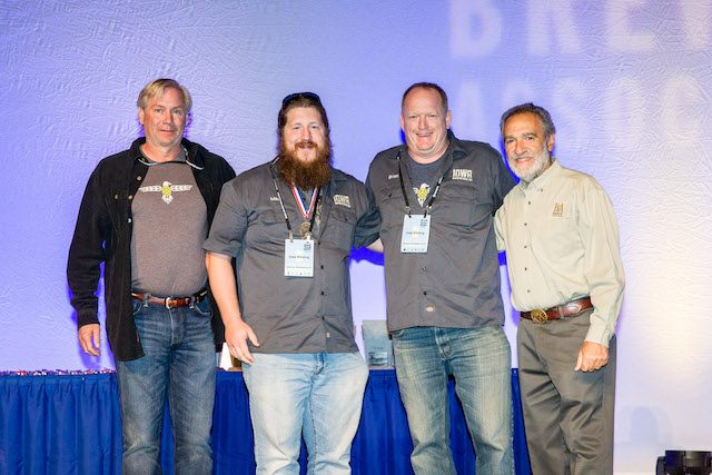 Matt Wolf, Mike Wing and Brian Stephan of the Iowa Brewing Company and Charlie Papazian from the Brewers Association as the Cedar Rapids brewery grabbed the silver medal at the 2016 Great American Beer Festival Competition for its Tragedy at the Commons beer. -- photo © 2016 Jason E. Kaplan​