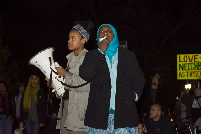 Asma Ali speaks alongside student organizer and West High senior Jade Merriweather on the Pentacrest. She encourages the community to welcome immigrants into the community as an opportunity to learn from each other. Tuesday, Nov. 15, 2016. -- photo by Zak Neumann