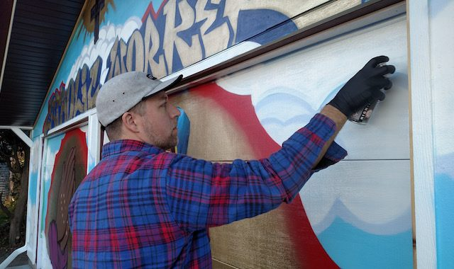 Mike Stenerson, of Iowa City, adds finishing touches on his mural at the Iowa City Catholic Worker Shelter House on Thursday, Nov. 10, 2016. -- photo by Lauren Shotwell