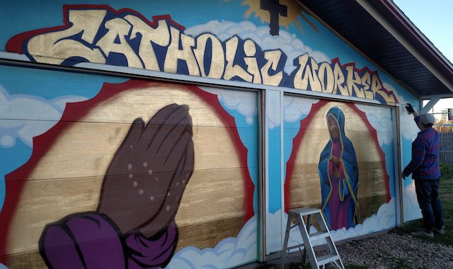 Mike Stenerson, of Iowa City, adds finishing touches on his mural at the Iowa City Catholic Worker House on Thursday, Nov. 10, 2016. -- photo by Lauren Shotwell