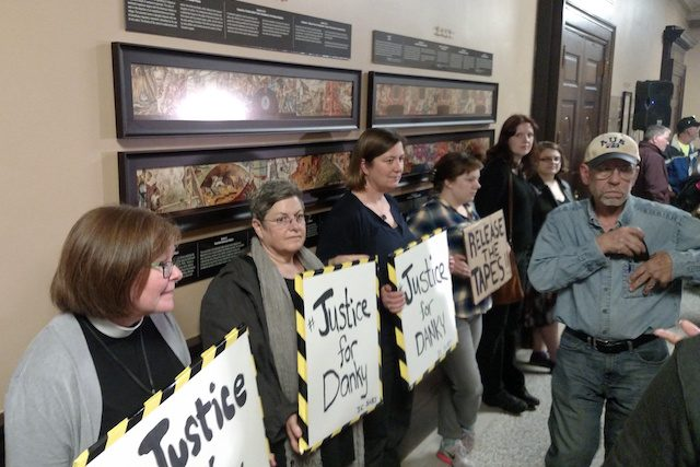 Individuals held signs outside the Cedar Rapids City Council Meeting on Tuesday, Nov. 15, 2016 in response to the officer-involved shooting of Jerime 'Danky' Mitchell. -- photo by Lauren Shotwell