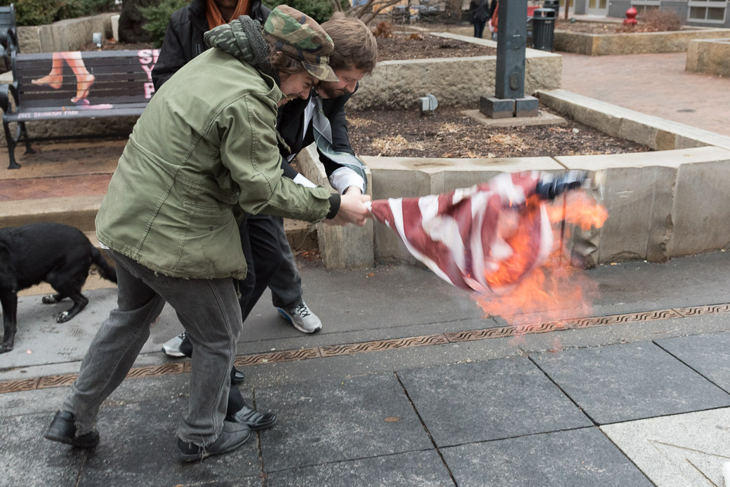 A man tries to wrestle a burning flag away from Andrew Alemao who lit it on fire as a protest on Friday, Jan. 20, 2017. -- photo by Zak Neumann
