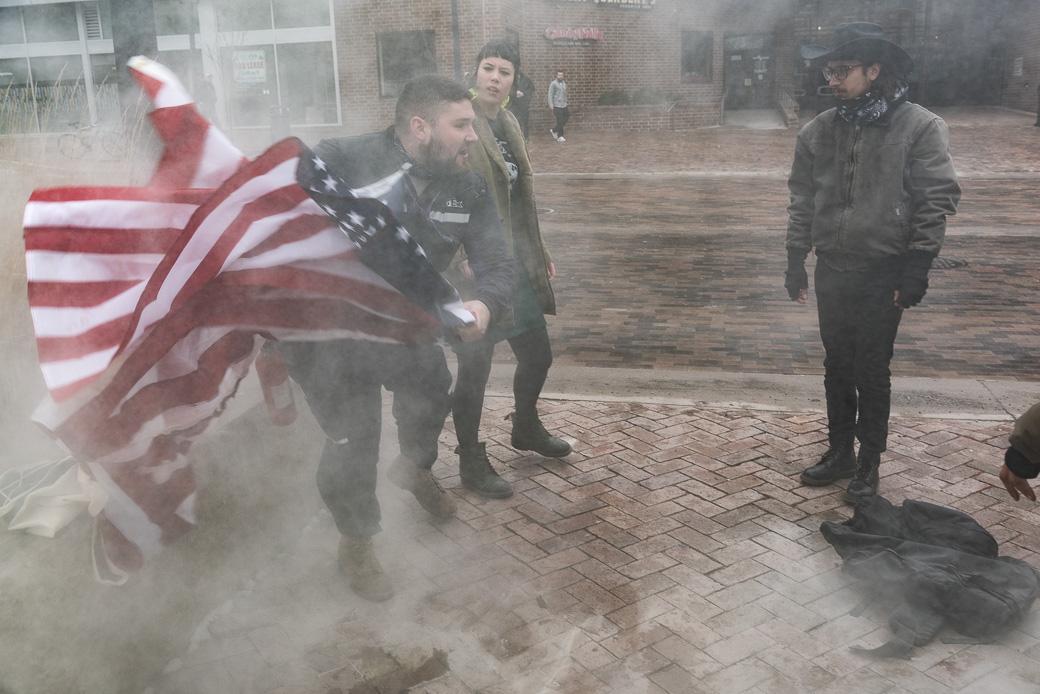 Matt Uhrin, Cedar Rapids, sprays a fire extinguisher and takes the flags from protestors Jordan Adams and Paul Osgerby on Thursday, Jan. 26, 2017. -- photo by Zak Neumann