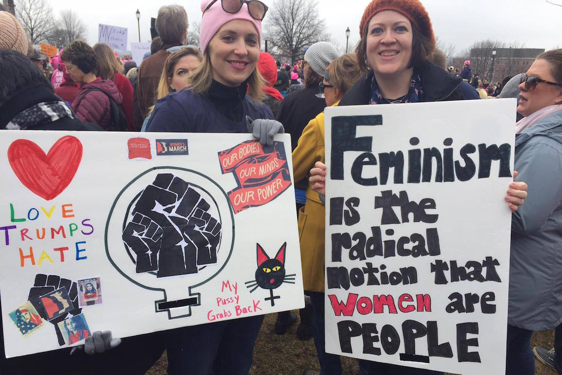 Kate Casaletto and Erin Duncan, two North Liberty moms who helped found the activist group Action Iowa, held up their signs during the Des Moines Women's March on Saturday, Jan. 21, 2017. -- photo by Christine Hawes